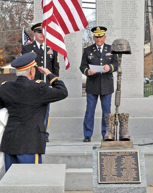 Col. Vivan Duffy salutes the battlefield cross memorial, which honors fallen soldiers, during the unveiling of the statue at the Wayne County Veterans' Memorial in Wooster Cemetery on Veterans Day.
