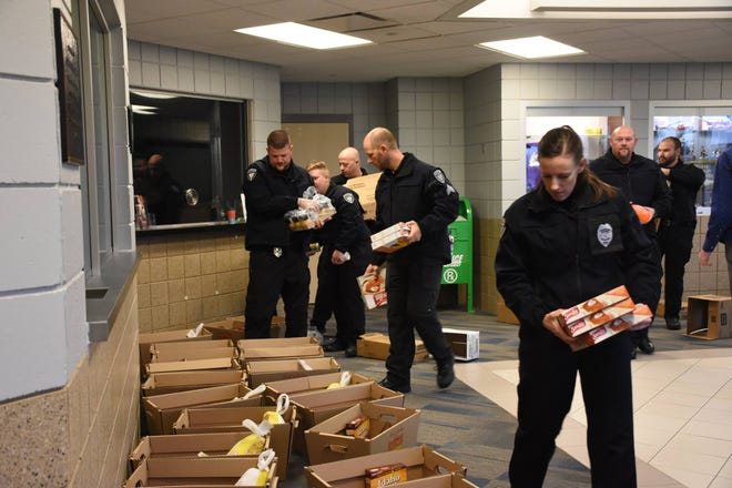 Members of the Waukee Police Department help fill Thanksgiving Baskets for area families in 2017.