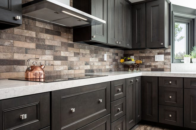 A stone backsplash makes a statement with  dark cabinets and cook top.