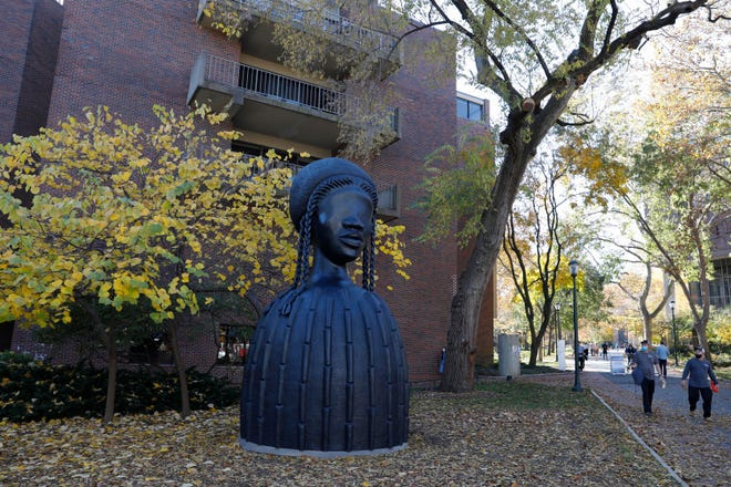 People walk past a newly installed sculpture by artist Simone Leigh on the campus of the University of Pennsylvania in Philadelphia. Leigh's 16-foot-tall bronze bust of a Black woman has been installed at the entrance to the heart of the campus.