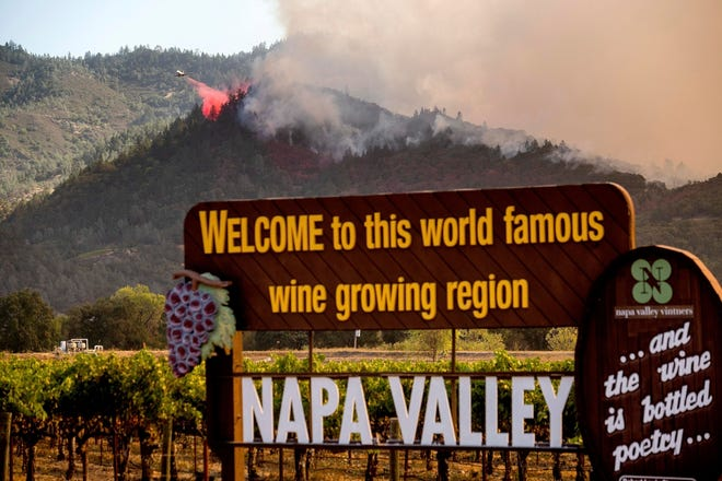 In this Sept. 27, 2020, file photo, an air tanker drops retardant on the Glass Fire burning in Calistoga, Calif. In three of the past four years, major wildfires driven by a changing climate have devastated parts of the world-class region, leaving little doubt that it's vulnerable to smoke, flames and blackouts during the fall.