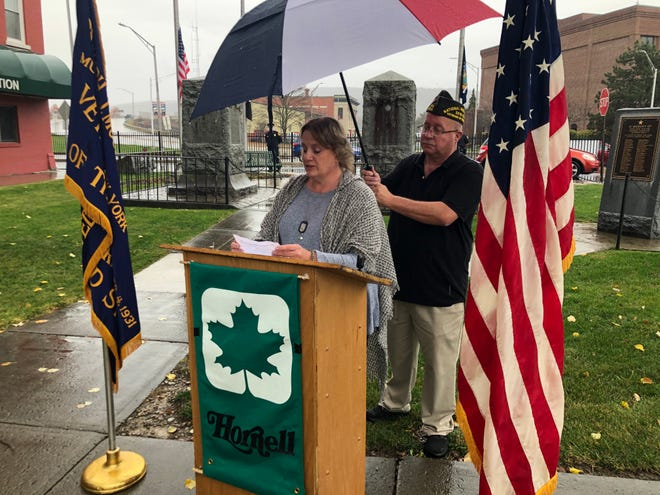 Gold Star Mother Kim Smith of Hornell speaks during a Veterans Day ceremony in front of the Broadway Mall veterans monuments on Wednesday, Nov. 11, 2020. Keith Cone, commander of Hornell VFW Post 2250, holds an umbrella for Smith.