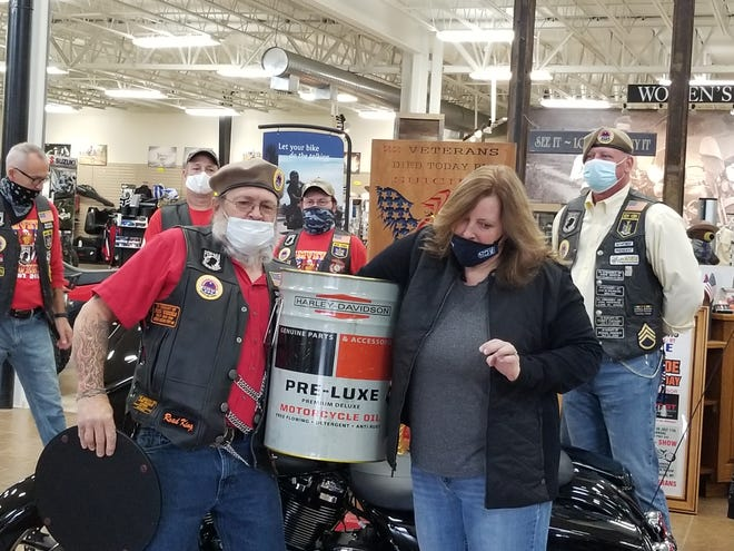 Roy Randall, president of the AMVETS Riders Post 245 of Hornell, and Jennifer Swarts, general manager and president of Arkport Cycles, draw the winning tickets in the AMVETS' fundraiser to benefit suicide prevention programs for veterans.