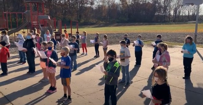 Dallas City, Illinois, Elementary School students perform a Veterans Day song for the school's video program Tuesday outside the school.