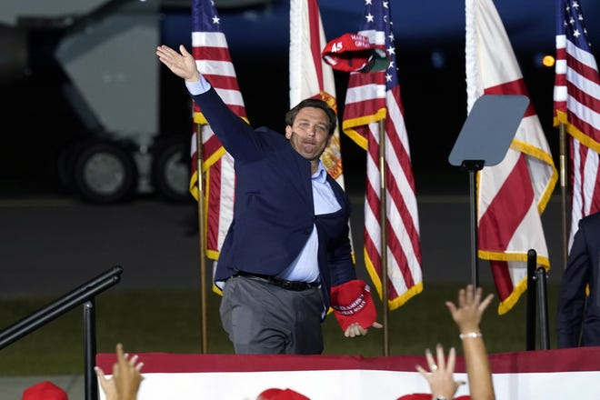 Florida Gov. Ron DeSantis throws campaign hats into the crowd for President Donald Trump at an Oct. 23 campaign rally in Pensacola.