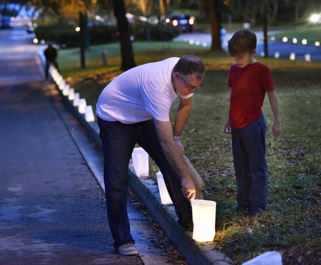 Ron Roessler and son Konrad, then 8, light candles during the Riverside Avondale Luminaria event in 2016. Riverside Avondale Preservation has purchased luminaria kits from Pine Castle.