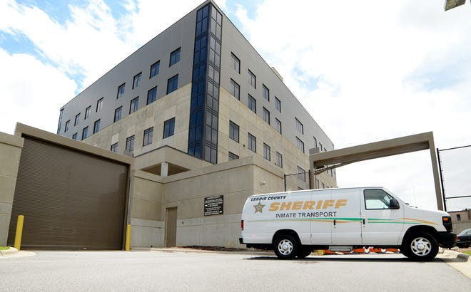 "A Lenoir County Sheriff inmate transport van is parked in front of the W.E. ""Billy"" Smith Detention Center gate."