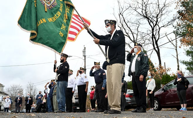 Mike Taddeo, front, holds the flag for the Italian American World War Veterans Post 40 as other veterans salute, during a Veterans Day ceremony  in Milford, Nov. 11, 2020.
