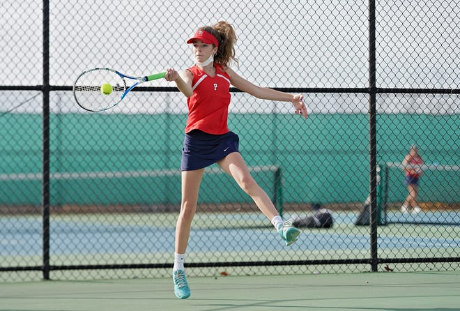 Kat Deus of Portsmouth leaps as she returns a shot during her No. 1 doubles match against Smithfield on Wednesday morning in Portsmouth.