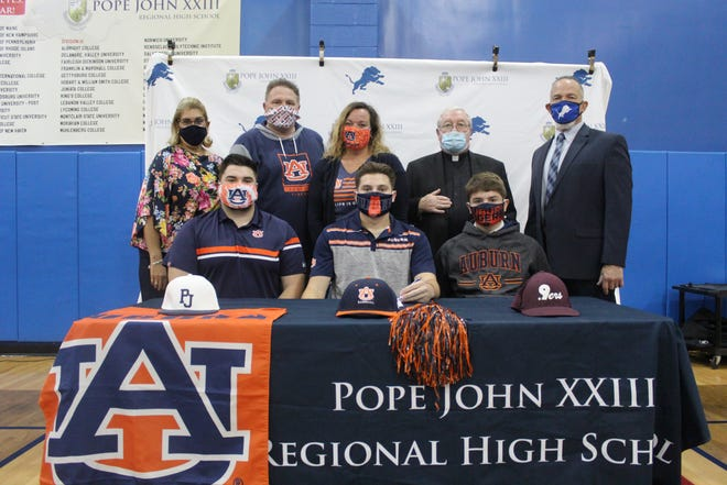 Pope John XXIII Regional High School senior Mike Bello, seated center, signs his National Letter of Intent to continue his academic and baseball careers at Auburn University on Wednesday at Pope John XXIII Regional High School in Sparta. Seated next to Bello, from left, are his brothers, Nick and Dominick. Standing in back are Pope John Athletic Director Mia Gavan, Bello's father and Pope John baseball coach Vin Bello, Bello's mother, Yvette, Pope John President Rev. Msgr. Kieran McHugh, and Pope John Principal Gene Emering.