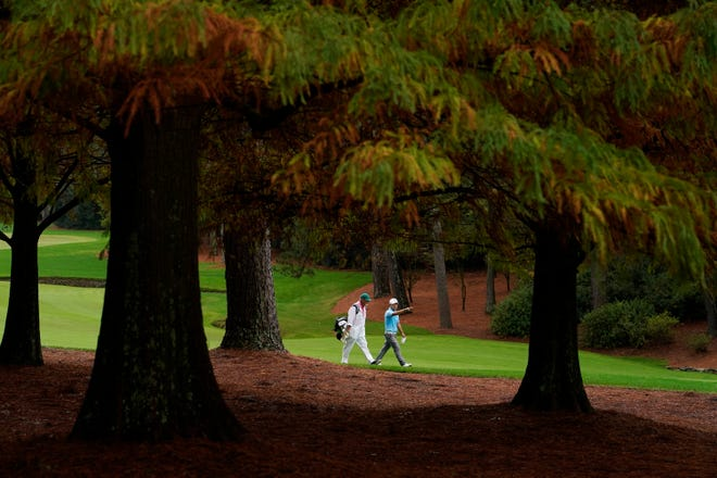 Sung Kang, of South Korea, walks with his caddie along the 13th fairway during a practice round for the Masters golf tournament Wednesday in Augusta, Ga.
