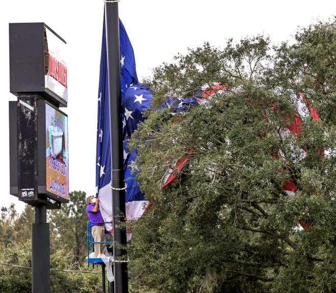 Jerry Jones, manager of the Georgia Floors Direct store on Southwest 17th Street in Ocala, was taking down the store's huge American flag on Wednesday in preparation for Eta to come through Marion County. The flag got caught in an oak tree while it was being taken down.