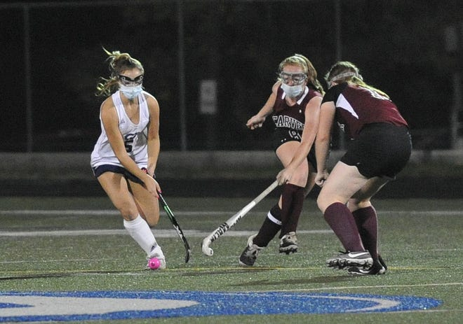 Cohasset's Ainsley Allen, left. keeps the ball away from Carver defenders Emily Stagnitta, center, and Ashleigh Johnson, right, during field hockey action at Cohasset High School, Tuesday, Nov. 10, 2020.