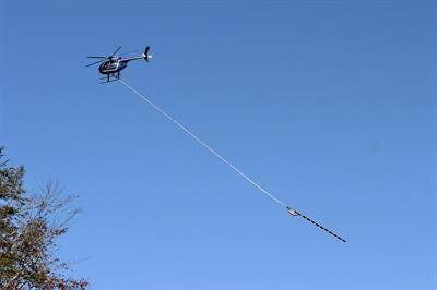 A helicopter working on behalf of Eversource tows a tree trimming tool recently in Antrim.