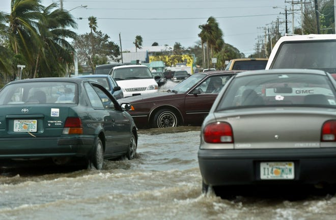 Drivers cope with a flooded intersection with inoperable traffic lights Wednesday morning in Key West after Hurricane Rita in 2005. [Lannis Waters/palmbeachpost.com]