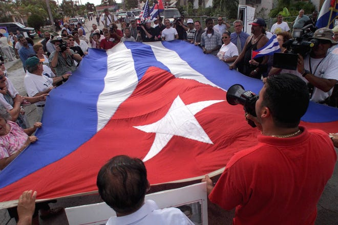 In April 2000, protesters surround a Cuban flag and shout anti- Fidel and anti-Clinton slogans in the street near the Miami home of Lazarus Gonzalez, great-uncle of  Elian Gonzalez, where Elian is staying. (LANNIS WATERS / The Palm Beach Post)