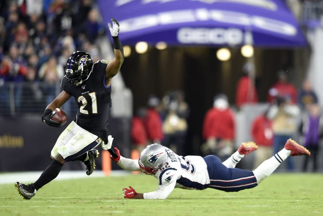 Ravens running back Mark Ingram eludes an tackle by Patriots linebacker Elandon Roberts for a long gain during the second half of last year's game in Baltimore. The Ravens finished with 210 yards rushing, 115 by Ingram.