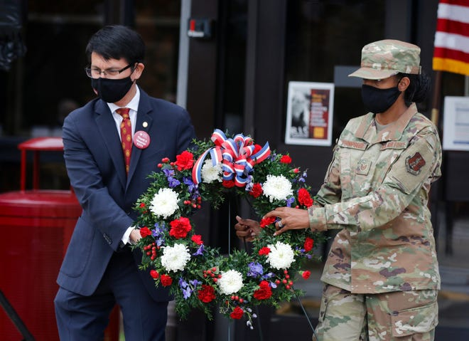 Rhode Island College President Frank D. Sanchez and Technical Sgt. Patrice Turnipseed, RI Air National Guard, a junior in the RIC School of Nursing, move a memorial wreath into place at the closing of the RIC Military Resource Center's first Veterans Day ceremony on campus Wednesday afternoon.