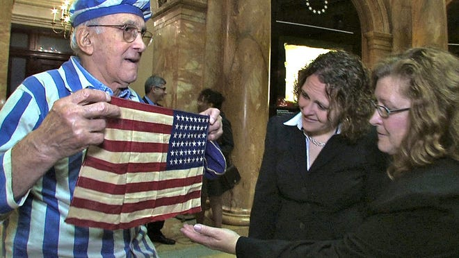 "Steve Ross, founder of the New England Holocaust Memorial, shows the flag that saved his life, to the granddaughter, Brenda Sattler, and daughter, Gwen Sattler Allanson, of the soldier who gave it to him at Dachau. He lived his life to honor that soldier and searched for him for 67 years. From the documentary ""Etched in Glass: The Legacy of Steve Ross."""