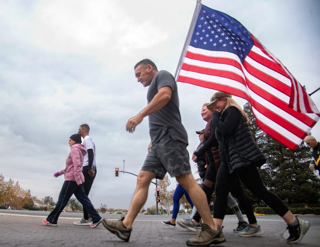 """Peter Vienna, center, carries a flag as he walks with about 30 other people down March Lane in Stockton during the 9 Miles for the 9 Heroes walk in Stockton. The walk remembers Vienna's stepson, Navy Corpsman Christopher """"Bobby"""" Gnem of Stockton, who was killed in a training accident along with eight Marines in Southern California."""