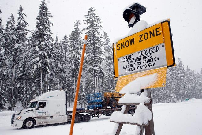 A truck crosses Willamette Pass in Oakridge as snow falls.