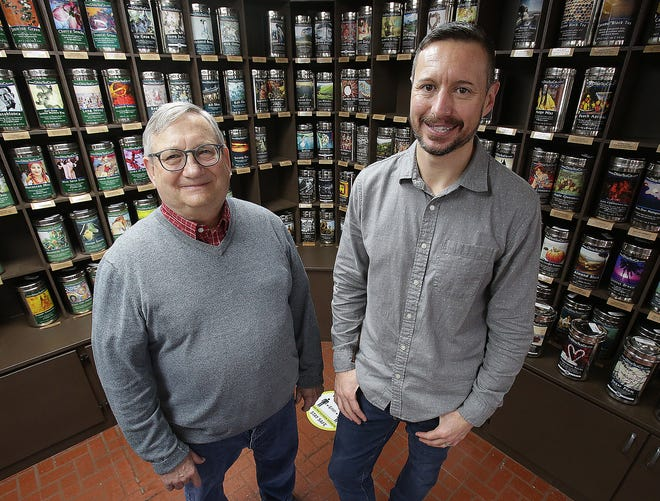 Terry Gabet ,left, and Kurt Gibbins , co-owners of the Ohio Tea Co., stand with a backdrop of about 400 different loose-leaf teas at the shop in Jackson Township.