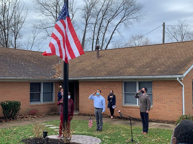 Ohio Secretary of State Frank LaRose and Nick Stilianos of the Pro Football Hall of Fame salute, while Richard Kirkland raises the flag. The Hall of Fame donated a flagpole to the Honor Home of Stark County. LaRose helped dedicate the pole during Veterans Day. Stilianos, director of facilities and operations at the Hall of Fame, suggested donating the pole.
