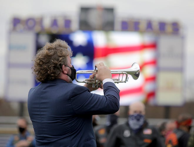 Sean Monigold, Jackson High School Jazz Band director, plays taps during a Veterans Day ceremony at Robert Fife Stadium. About two-dozen U.S. military veterans watched from the turf at the stadium's 50-yard line, while a handful sat in the bleachers or stood next to the football field.