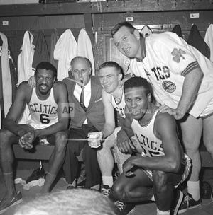 In this April 9, 1964, Boston Celtics, from left, Bill Russell, coach Red Auerbach, Tommy Heinsohn, Jim Locustoff, and K.C. Jones celebrate in the locker room after clinching their eighth straight Eastern Division playoff title at the Boston Garden in Boston. Tommy Heinsohn, who as a Boston Celtics player, coach and broadcaster was with the team for all 17 of its NBA championships, has died. He was 86. The team confirmed Heinsohn's death on Tuesday, Nov. 10, 2020.