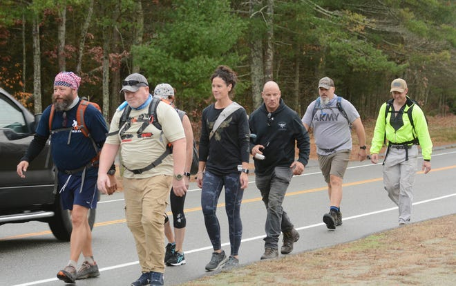 Darryl Lane of Sterling, left, and  Steve Bates of Plainfield, to his right, join Darryl Lane of Sterling, Kate Eberle of Colchester, Beth McGonagle of Southborough, Mass., Brian Sullivan of Colchester, Jim Turner of Plainfield and Craig Plante of Franklin Wednesday walking 22 miles through Griswold and Plainfield to raise awareness and pay tribute to the 22 veterans who commit suicide every day. [John Shishmanian/ NorwichBulletin.com]