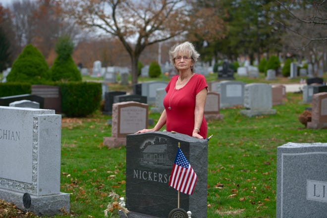 Ruth Nickerson visits her husband's grave in Hope Cemetery in Worcester on Wednesday. It is decorated with an American flag she placed there in time for Veterans Day, to replace one that she found missing last week.