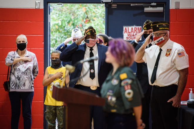 Veterans salute as the national anthem is sung at a Veterans Day ceremony at Hope Mills Recreation Center on Wednesday.