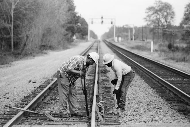 Two men work on railroad tracks in Robeson County on Nov. 14, 1989.