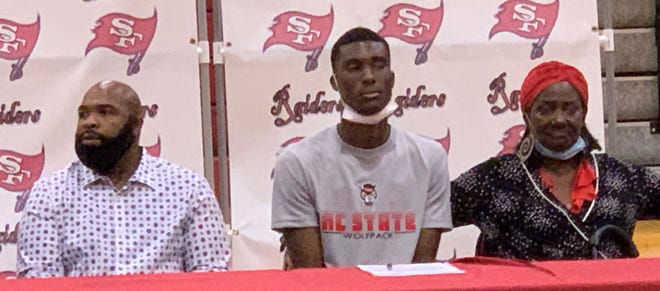 Santa Fe High School's Ernest Ross at his signing ceremony Wednesday at the Raiders gym in Alachua. Grandmother Rosemary Hill is at right and custodian Charles Wakeley is at left.