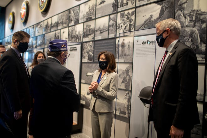 Richard Drago, commander of the Military Order of the Purple Heart, left, presents Lt. Gov. Kathy Hochul with a challenge coin at the dedication of the newly expanded National Purple Heart Hall of Honor in New Windsor, N.Y., on Nov. 11, 2020.