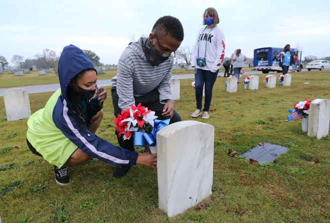 Students from Arts 'n Autism decorate the graves of veterans in Tuscaloosa Memorial Park Tuesday, Nov. 10, 2020, in preparation for Veterans Day. Kelsey Merriweather helps CJ Bryant place a vase beside a headstone. [Staff Photo/Gary Cosby Jr.]