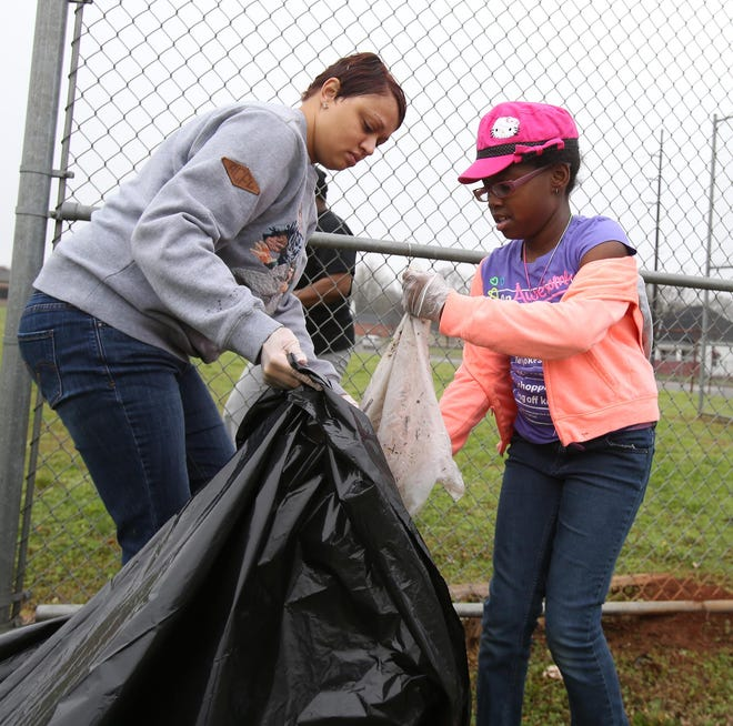 Mashieka Odom is seen in this file photo from 2015 holding open a trash bag for her niece, Arica Williams, to deposit trash into as they participate in the Burrell Odom Day of Service t clean up litter around west Tuscaloosa. A similar clean-up event is planned for Saturday at Burrell Odom Park. [Staff file photo/Erin Nelson]