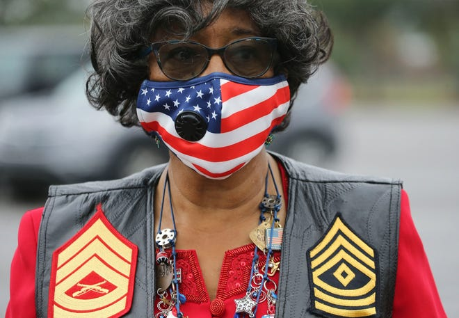 The traditional Veterans Day observance at Tuscaloosa Veterans Park was converted to a drive-in event Wednesday, Nov. 11, 2020. Yvonne Wells, wife and mother of veterans, is dressed in patriotic regalia. Wells led the Pledge of Allegiance.  [Staff Photo/Gary Cosby Jr.]