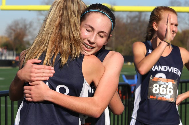 Grandview sophomore Greta Tew is hugged by freshman teammate Maddie Palmisciano after the Division III state cross country meet Nov. 7 at Fortress Obetz. The Bobcats girls team reached state for the first time since 2012.