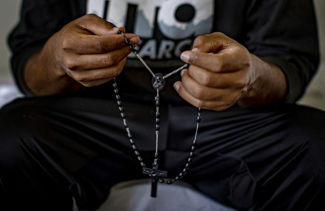 Tsegai 30, who fled persecution in Eritrea over being a member of an ethnic minority, holds a rosary given to him by family members while staying in a church on September 22, 2020, in San Bernardino County.