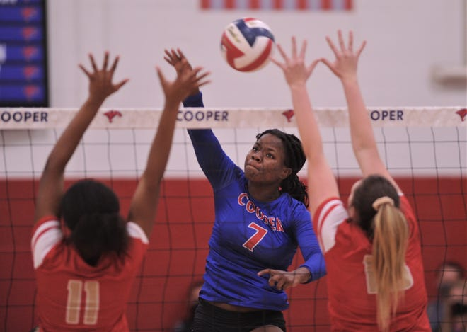 Cooper's Dazz Larkins slams the ball between two Lubbock Coronado defenders. Larkins had a team-high 15 kills in the Lady Coogs' 3-1 loss to Coronado on Tuesday, Nov. 10, 2020, at Cougar Gym.