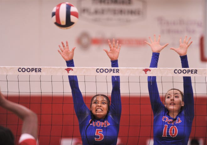 Cooper's Emani Davis (5) and Bri Garcia (10) defend at the net against a Lubbock Coronado shot in a District 4-5A match on Nov. 10 at Cougar Gym. Davis returns from last year's team.
