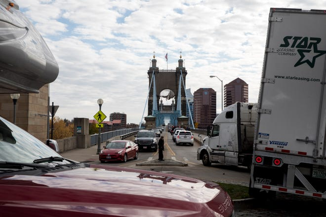 A semi-truck drives over a medium on the round about onto the Roebling Suspension Bridge on Wednesday, Nov. 11, 2020, in Cincinnati.