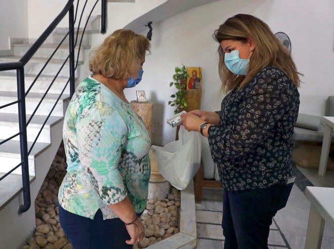 Nadine Sokhn, kanan, perawat sukarelawan di sebuah klinik amal, berbicara dengan Mireille Saadeh, seorang pasien yang datang mencari pengobatan gratis untuk mengobati penyakit kronisnya, di lingkungan Achrafiyeh di Beirut, Lebanon, Senin, 2 November 2020.