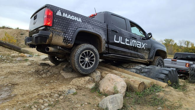 A Chevy truck high centers over a rock/timber obstacle at Holly Oaks ORV Park.