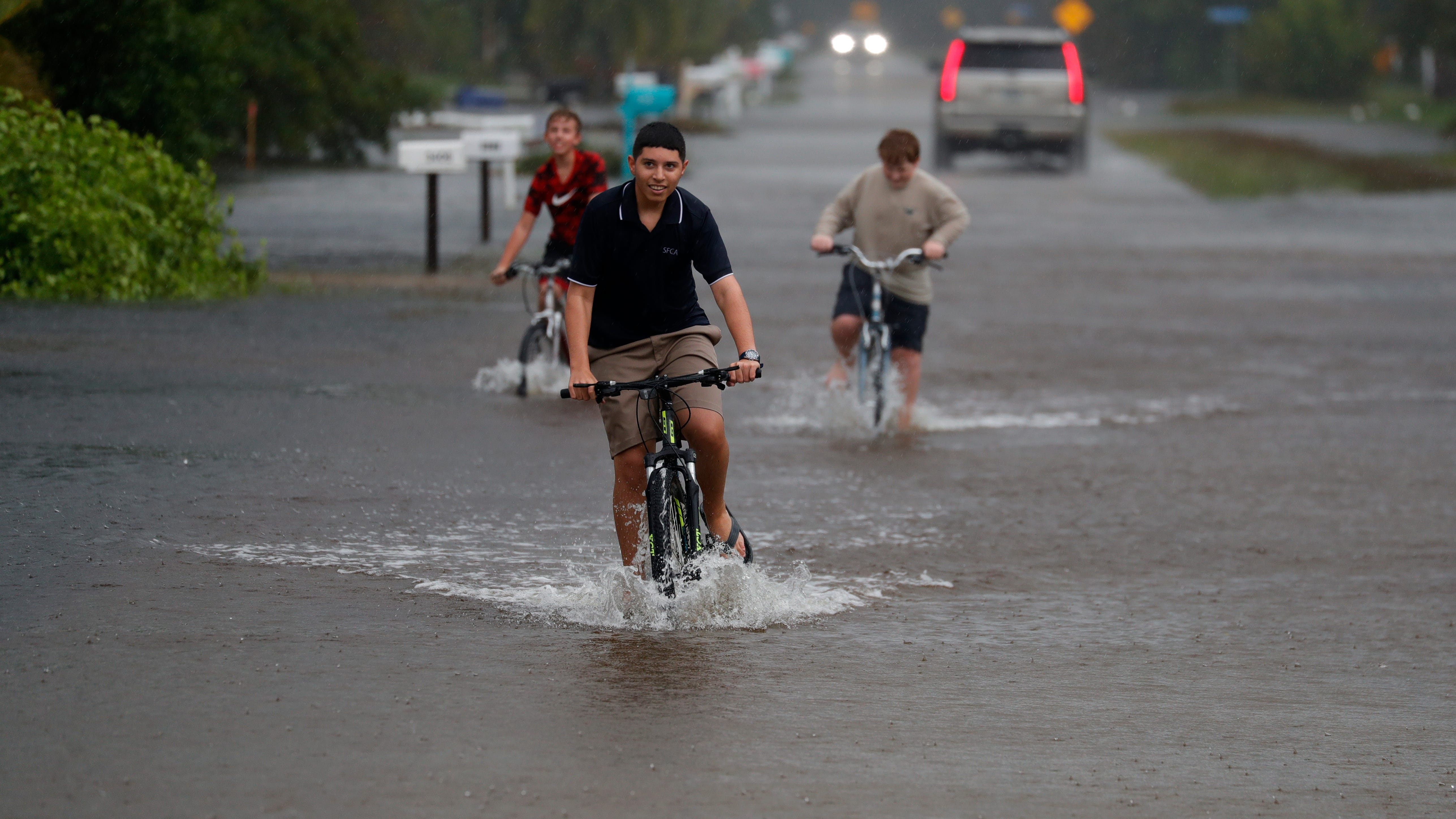 Jayden Diaz, 14, along with friends Kayden Hallmon, 12, left, and Randy Hanshaw,14, ride their bikes through flooded 8th Avenue and Oleander Street in St. James City Wednesday, Nov, 11, 2020. The strong winds and rain from Hurricane EtaÊwere impacting the area.