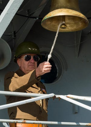 James Goodall rings the bell of the LST 325 21 times to honor veterans during a Veteran's Day ceremony held on the deck of the LST 325 docked along the riverfront in Evansville, Ind., Wednesday morning, Nov. 11, 2020.