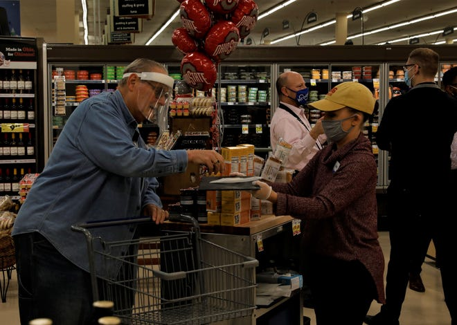 Tom Kelley, left, gets a sample from Audra Brown at the new Murray's Cheese and Culinary kiosk on Wednesday, Nov. 11., in the Kroger store located on Main Street in Lancaster.