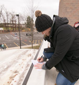St. Patrick School Principal Carley Dunphey provides a requested autograph from fifth-grader Mia Van Riper, below, as Dunphey spends the day working and interacting with the students from the roof of the school Wednesday, Nov. 11, 2020. Using a bucket attached to a rope, notes were passed back and forth from students who won the honor of seeing their principal on the roof by achieving their reading goals.