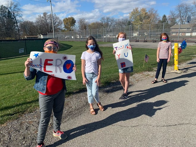 Pleasant Middle School students Emma Bradac, Lilly Gleespen, Lydia Baumgartner and Macy Hamper show their appreciation for veterans during the Veterans Day drive-thru ceremony Tuesday, Nov. 10, 2020.